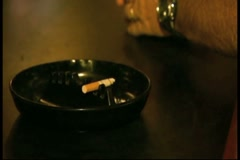 Smoking cigarette in ashtray with man holding beer can sitting at a bar Stock Footage