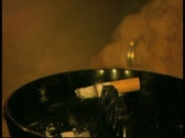 Cigarette smoking in ashtray then pan to beer in glass Stock Footage