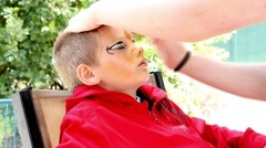 Time lapse of cute boy getting face paint of a tiger applied - stock footage