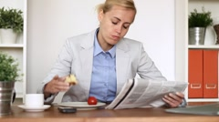 Young happy businesswoman having breakfast while reading the newspaper - stock footage
