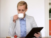 Young businesswoman having breakfast while working on digital tablet NTSC Stock Footage