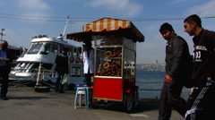 Turkey Istanbul Turkish Simit bread vendor at ferry pier Stock Footage