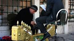 Turkey Istanbul shoe shiner polishing customer shoes Stock Footage