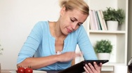 Young woman with digital tablet by the table in home, dolly shot HD Stock Footage