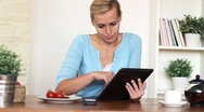 Woman eating breakfast and surfing the net on digital tablet, dolly shot Stock Footage