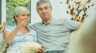 Attractive Mature Couple Watching TV with Popcorn Stock Footage