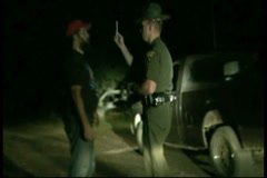 Suspected drunk driver being tested by police officer Stock Footage