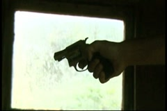 Firing revolver in front of window Stock Footage