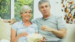 Mature Couple Eating Popcorn in Front of TV Stock Footage