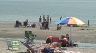 Stock Video Footage of People enjoying the beach under umbrellas. (2 of 4)