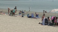 Stock Video Footage of People opening folding chairs on the beach.