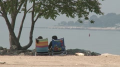 Two people sitting in folding chairs looking at the water. (1 of 2) Stock Footage