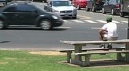 Stock Video Footage of A man sitting on a picnic bench watching traffic.
