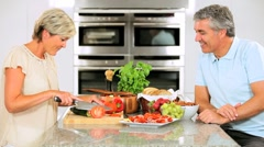 Mature Couple in Home Kitchen Preparing Lunch Stock Footage