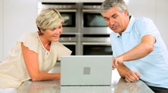 Middle Aged Caucasian Couple in Home Kitchen Using Laptop Stock Footage
