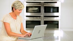 Attractive Mature Lady Working on Laptop in Kitchen Stock Footage