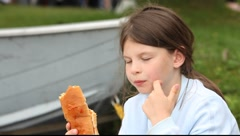 girl eating hot dog outdoor - stock footage