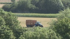 Tractor towing trailer stops in field. Stock Footage