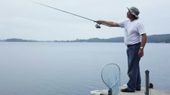 Man casting off a dock and fishing. Stock Footage