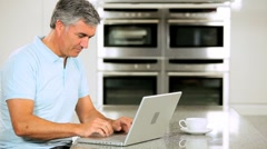 Mature Male Using Laptop Pleased with Online Results Stock Footage