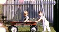 Stock Video Footage of KIDS Pushing Baby Brother Red Toy Wagon 1950s Vintage Film 8mm Home Movie 685
