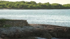 stone structure on the beach with island in background - stock footage