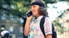 Young boy talking on mobile phone in the city, steadicam shot HD Stock Footage