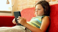 Stock Video Footage of Young teenager with ebook reader on sofa, steadicam shot HD