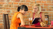Happy female friends with tablet computer in pub, steadicam shot HD Stock Footage