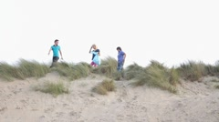 Teenagers walking and cleaning dunes Stock Footage