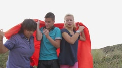 Group of teenagers playing with red blanket Stock Footage