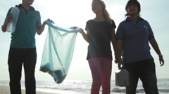 Teenagers with adult Volunteering Beach Cleanup Stock Footage