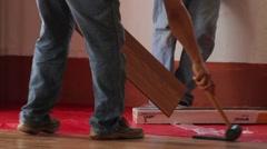 Carpenters man working on wood floore installing Stock Footage