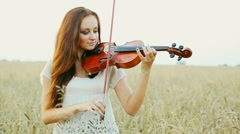 Young girl playing violin over nature Stock Footage