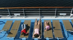 Mother with two children sunbathing and playing games on sunbed on ship deck Stock Footage