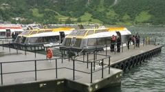 Liner rescue boats depart from small village port Stock Footage