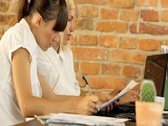 Two young businesswomen working with papers in office, steadicam shot Stock Footage