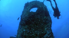 A diver swims around a shipwreck from a low angle. Stock Footage