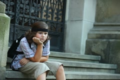 Young lonely sad boy sitting on stairs, steadicam shot Stock Footage