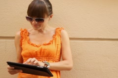 Happy attractive woman with tablet computer in the city, steadicam shot Stock Footage