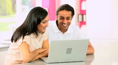 Young Ethnic Couple Online with Wireless Laptop Stock Footage