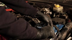 Auto mechanic repairing a part of a car engine - stock footage