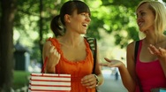 Happy young female friends with shopping bags in the park, steadycam shot Stock Footage