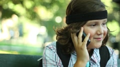 Portrait of young boy talking on mobile phone in the city, steadicam shot Stock Footage