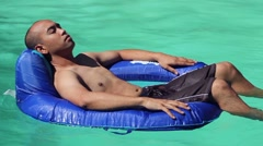 Asian Man Relaxing in Floating Pool Chair - stock footage