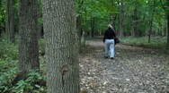 Stock Video Footage of Woman with small dog walk on trail in autumn