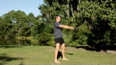 Man swinging a kettlebell in the park Stock Footage