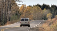 Stock Video Footage of White Van Passes around Rural Corner in Autumn