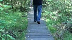 Man Walking on Boardwalk Stock Footage