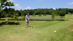 Adult male driving a golf ball with lake in background. Stock Footage